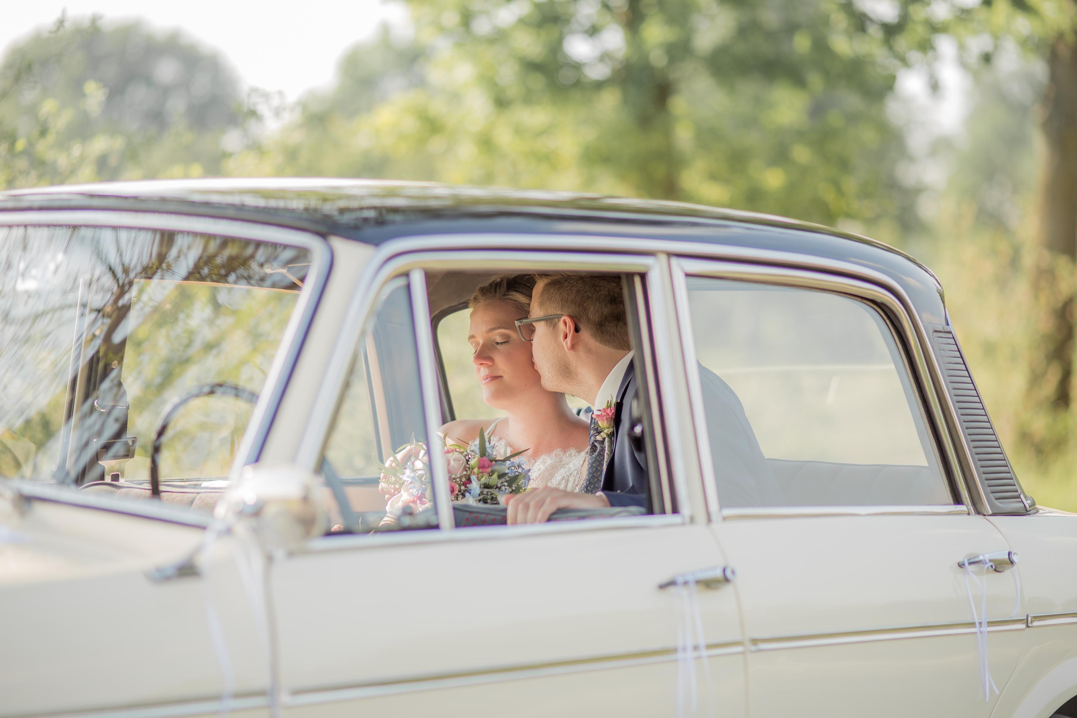küssendes Paar im Oldtimer während einer Hochzeit nähe Münster